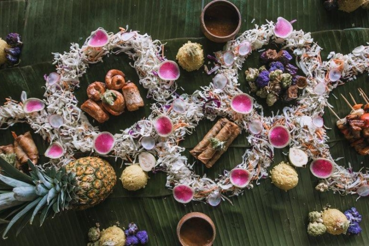 Food is arranged and served on a table lined with banana leaves as Eats by E kamayan pop-up dinners.