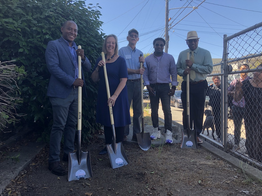 Five adults pose with shovels, sticking slightly into a dirt ground.
