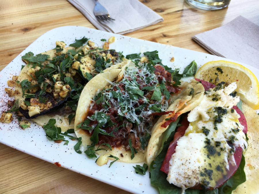 A plate of tacos: Three Sisters (roasted summer squash, sweet corn and black bean puree); The Caprese (fresh heirloom tomato, basil and mozzarella) and the Original (Italian sausage, tomato sauce, parsley and Parmesan cheese).
