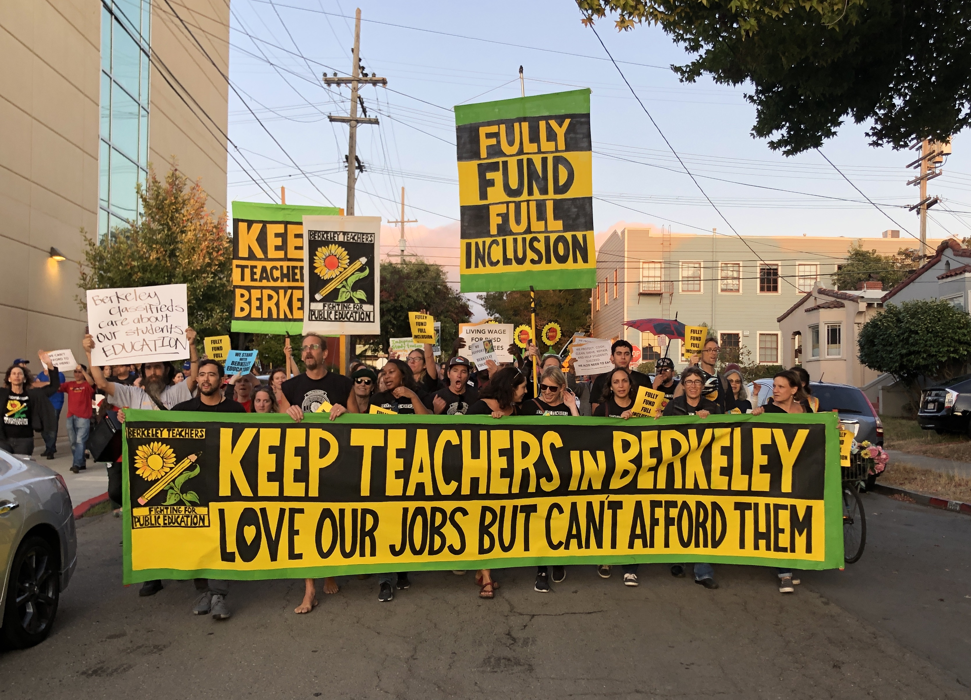 Mass of protesters in the street, carrying banners supporting Berkeley teachers