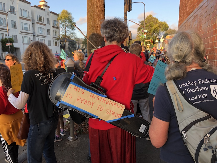 "a person dressed in red has their back to the camera. they're wearing an instrument case that has a sign on it: ""this instrument is ready to strike"""