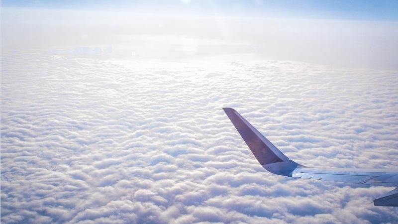 Airplane tail flying above bed of clouds