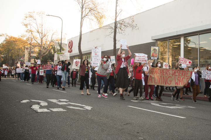 Protesters in red march in a street. Some are wearing masks or holding signs