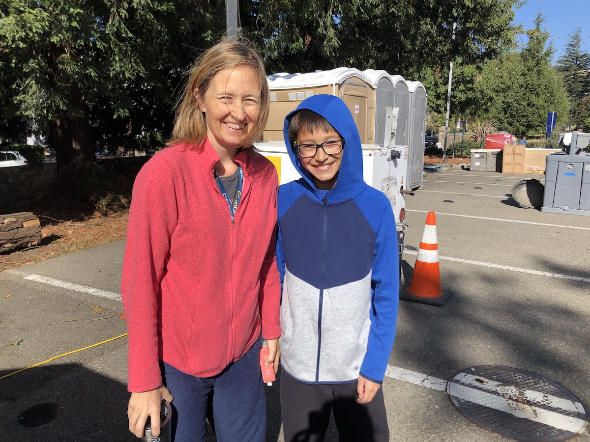 a middle-aged woman in a pink jacket stands next to boy, 12, wearing a hood. They're grinning. Portable toilets are visible in the background.