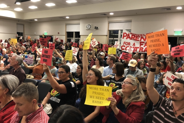 """A packed room of seated protesters, wearing red and holding signs that say """"More than praise, we need a raise."""""""