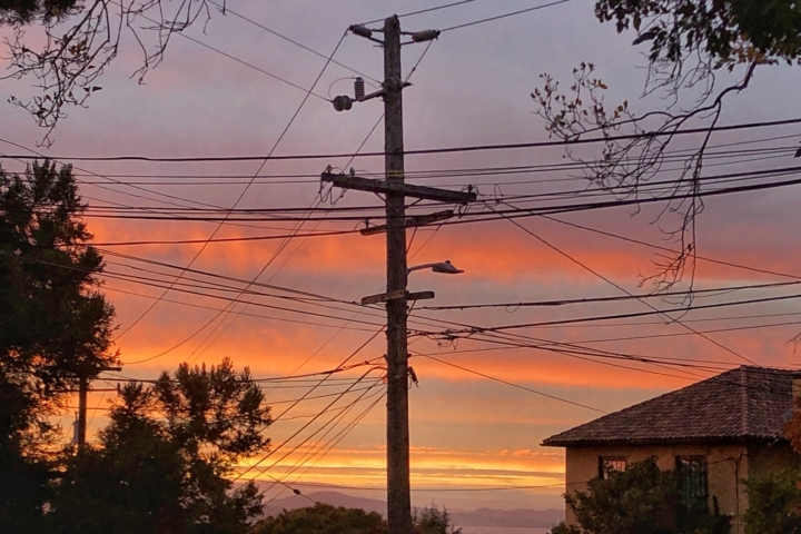 Power lines with sunset in the background