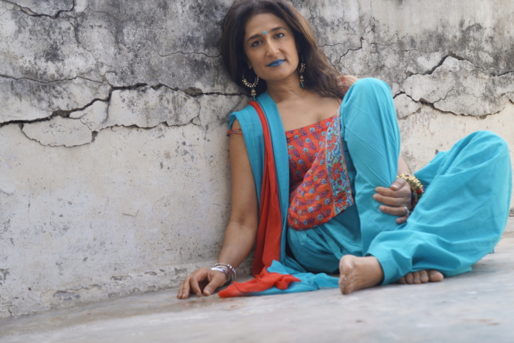 woman in turquoise sitting against wall