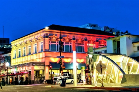Passione Cafe and BART entrance in downtown Berkeley lit up in dusk light
