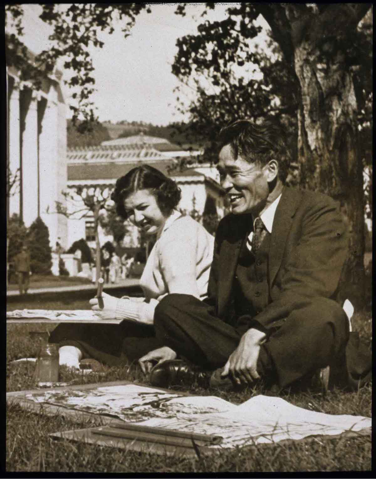 old black and white picture of a Japanese man sitting outside with a young woman. both have art materials in front of them