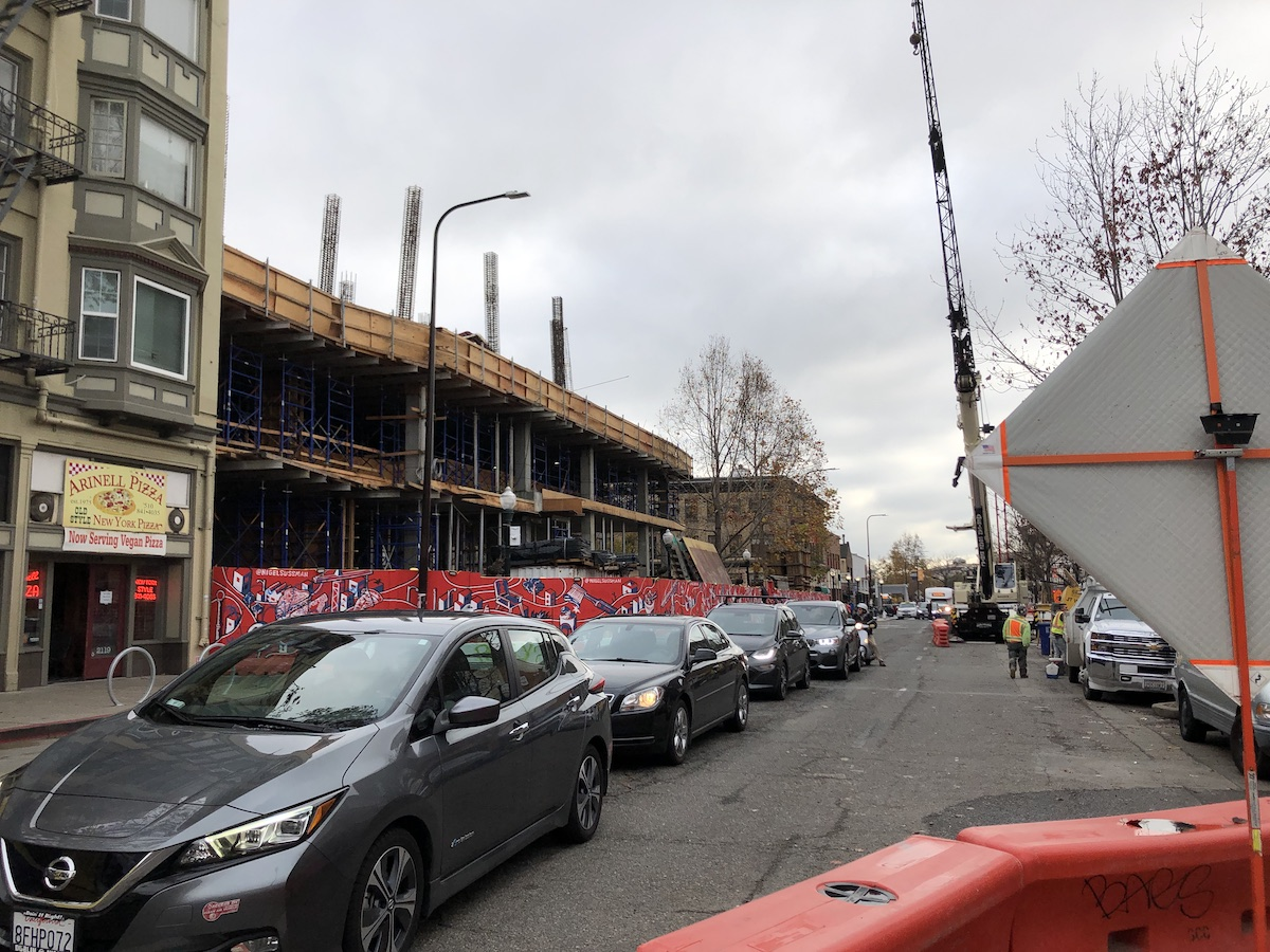Cars line up on a narrow streets. Barriers are up for construction work and a building is under construction in the background.