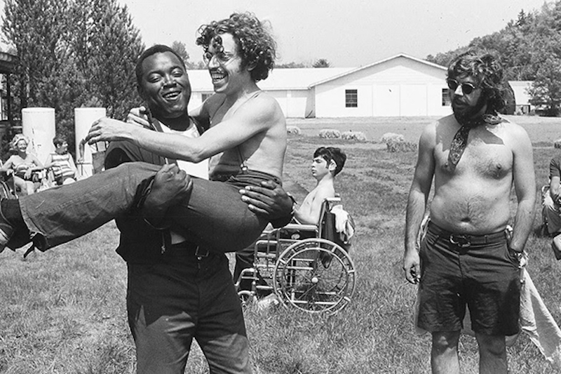 man holding another man at a summer camp