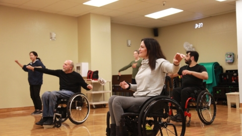People in wheelchairs reach their arms out
