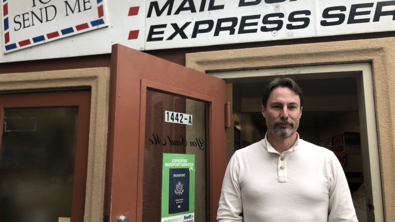 a middle-aged white man stands in front of a postal shipping storefront