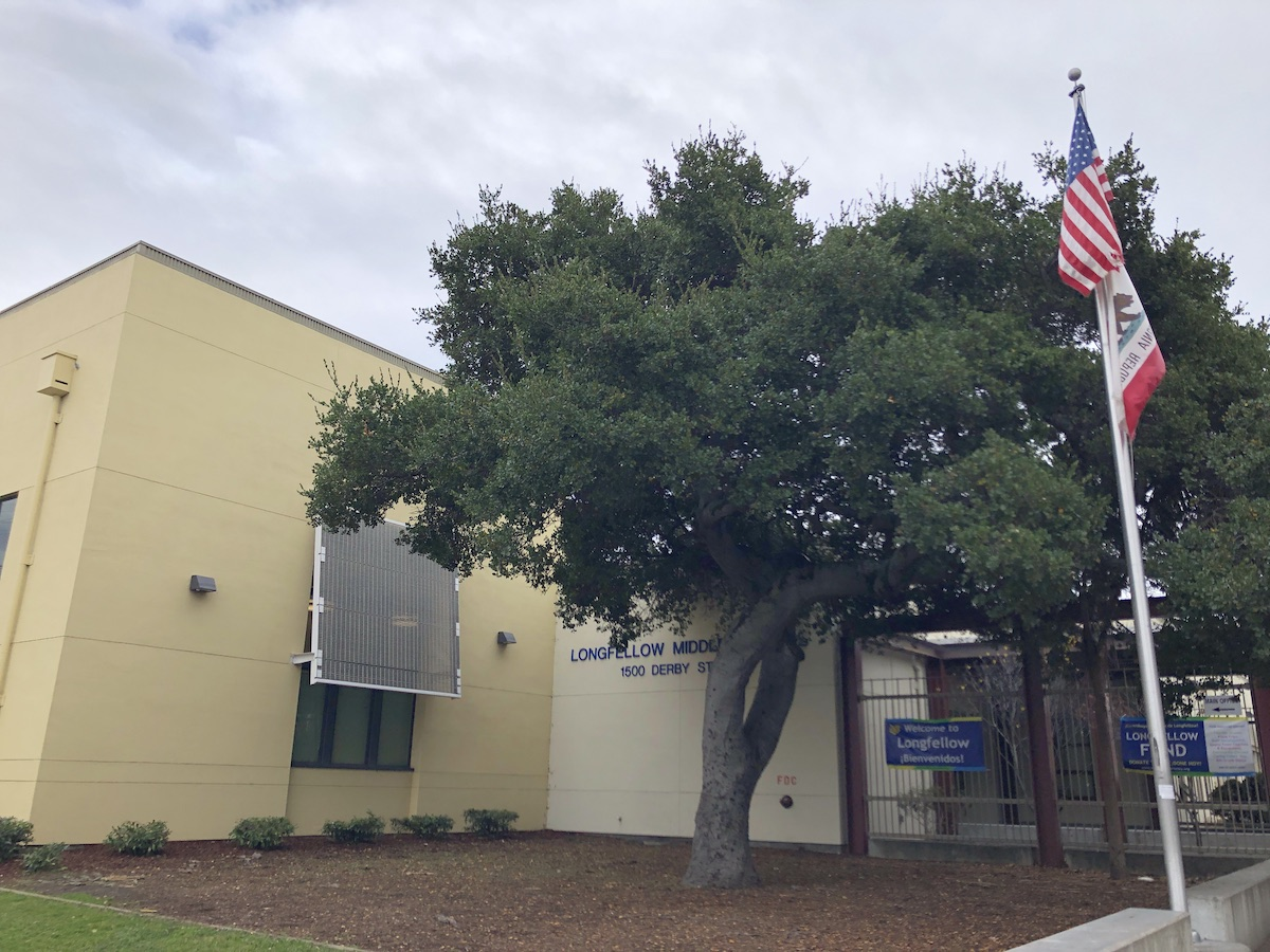 a yellow school building with a tree and flagpole in front of it