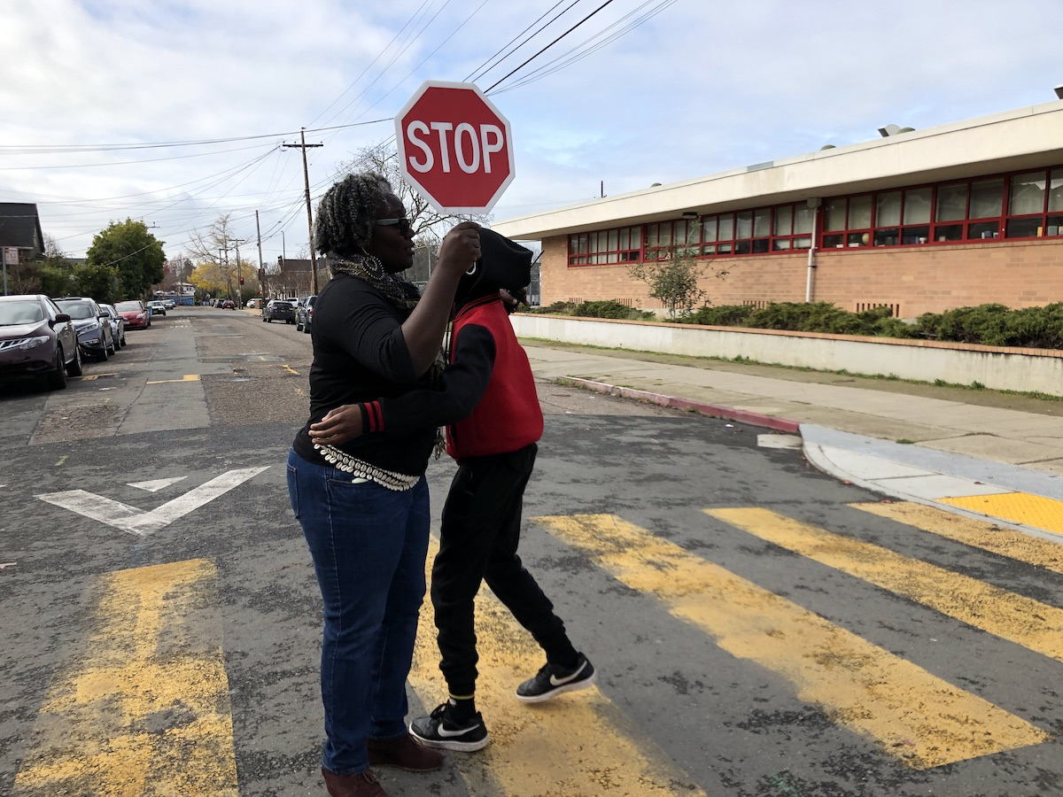 A kid hugs an adult in the middle of a crosswalk. The adult is holding a small stop sign