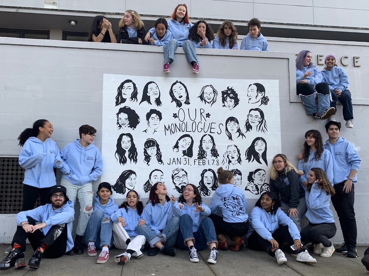 About 20 smiling teenagers gather around a mural of their faces. They're all wearing the same blue sweatshirt and some are dangling their legs off a ledge