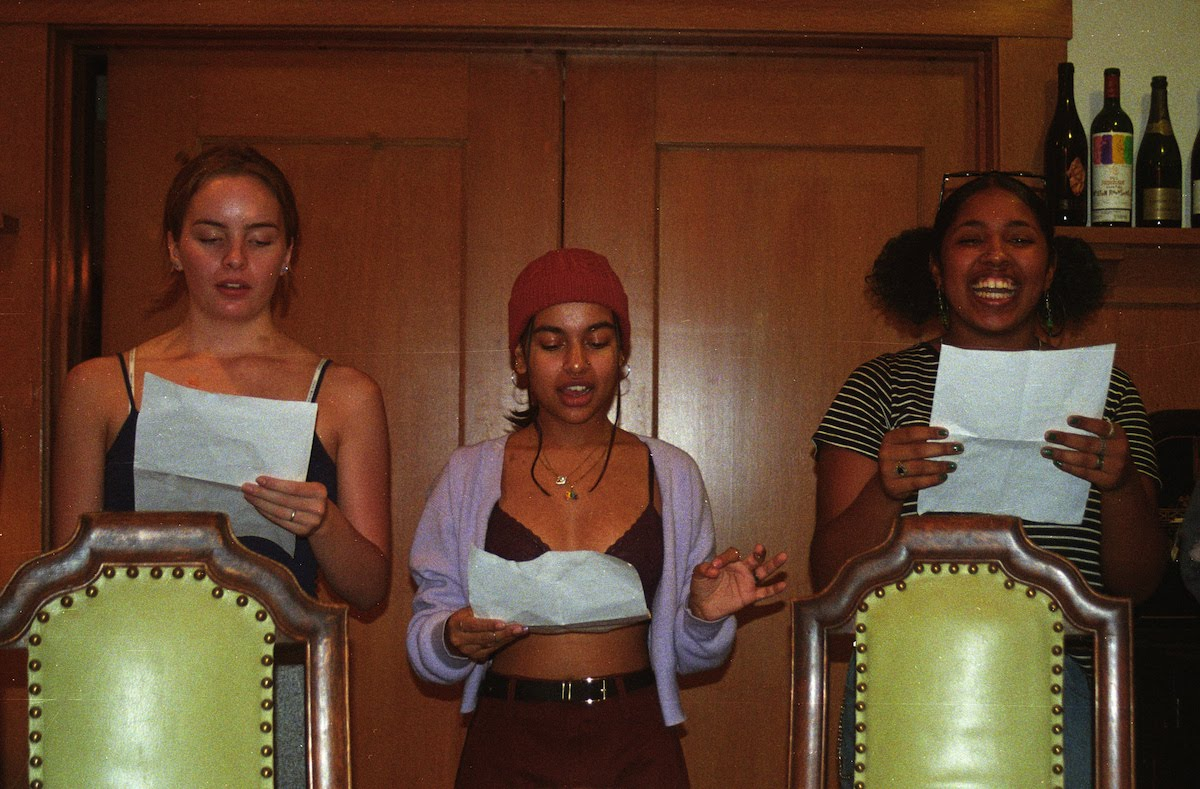 Three teenage girls read from pieces of paper. One is laughing.