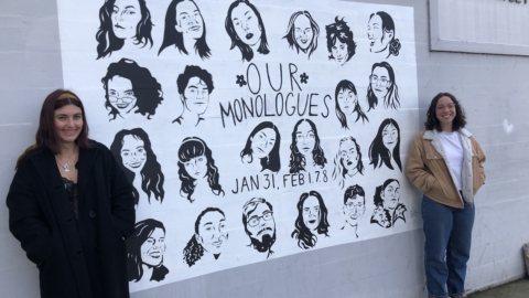"Two teenage girls stand against a building. Between them is a mural that says ""Our Monologues"" and features paintings of a bunch of faces."