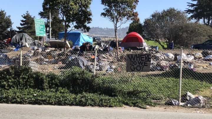 "a few tents and lots of trash on the ground. a handwritten sign on a fence says ""Where do we go?"""