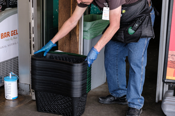 Michael, a Whole Foods employee sets out a stack of disinfected baskets for shoppers entering the store at Telegraph Avenue in Berkeley.