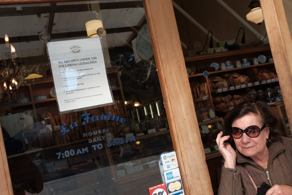 A customer emerges from La Farine bakery on College Avenue which is open for limited hours and under strict guidelines, such as no outside seating. Photo: Pete Rosos