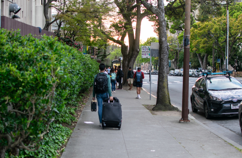 student rolling suitcase down sidewalk
