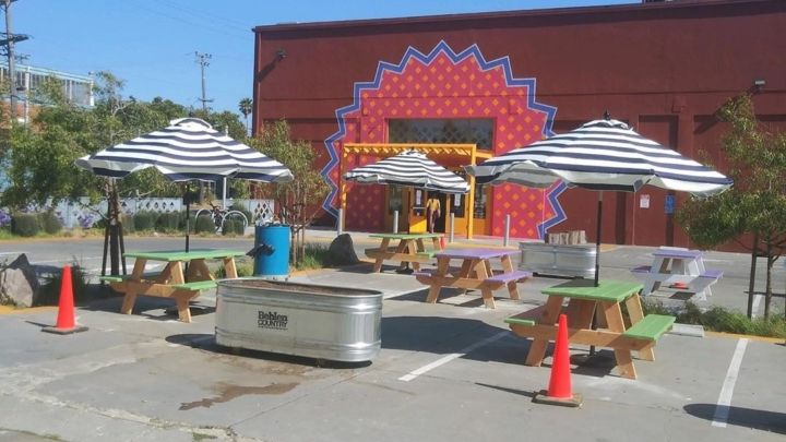 Colorful picnic tables and outdoor umbrellas are set up in the private parking lot connected to Vik's Chaat in Berkeley.