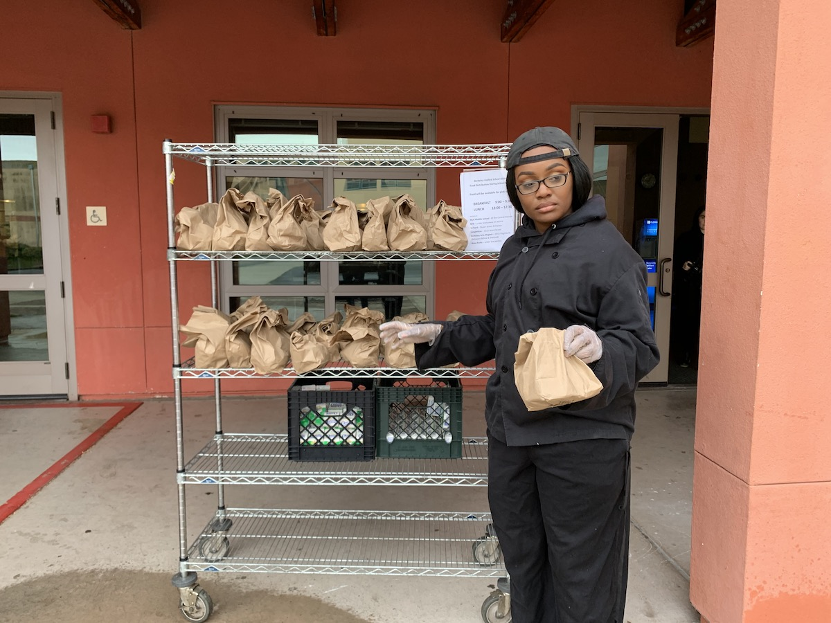 A woman, dressed in black and with gloves on, stands in front of a cart holding a number of brown bagged meals