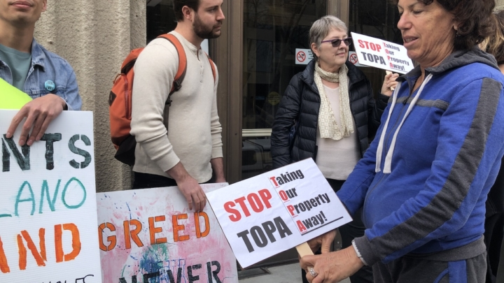"Two men hold signs that say ""Greed"" and two women hold signs that say ""Stop TOPA"""