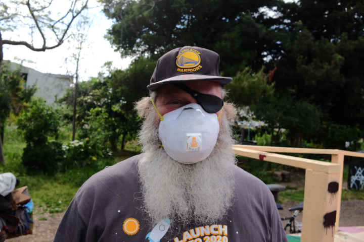Food Not Bombs volunteer Timothy Busby with mask at People's Park.