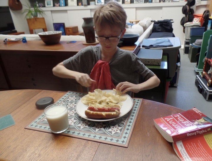 Nine-year-old Leo proudly enjoys a hot dog he cooked for himself.