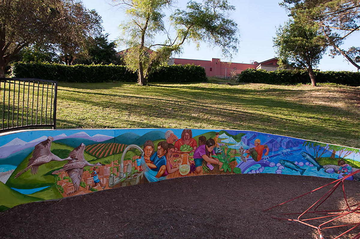 Colorful long skinny mural curves around, with hill in the background and sand in front