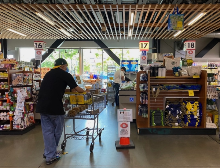 A customer waits for the shopper before him to complete his transaction at Berkeley Bowl West. Photo: Sarah Han