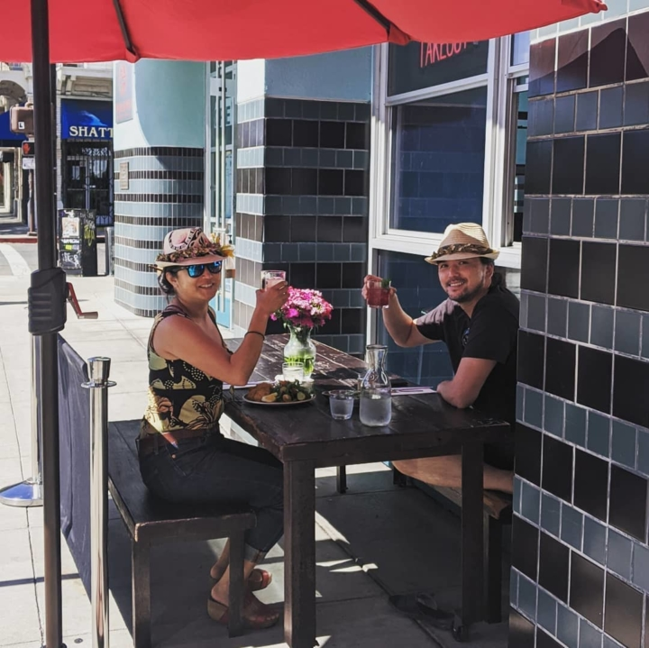 Two customers sitting under an umbrella on Fish & Bird's small patio space hold up drinks in a toast. Photo: Fish & Bird