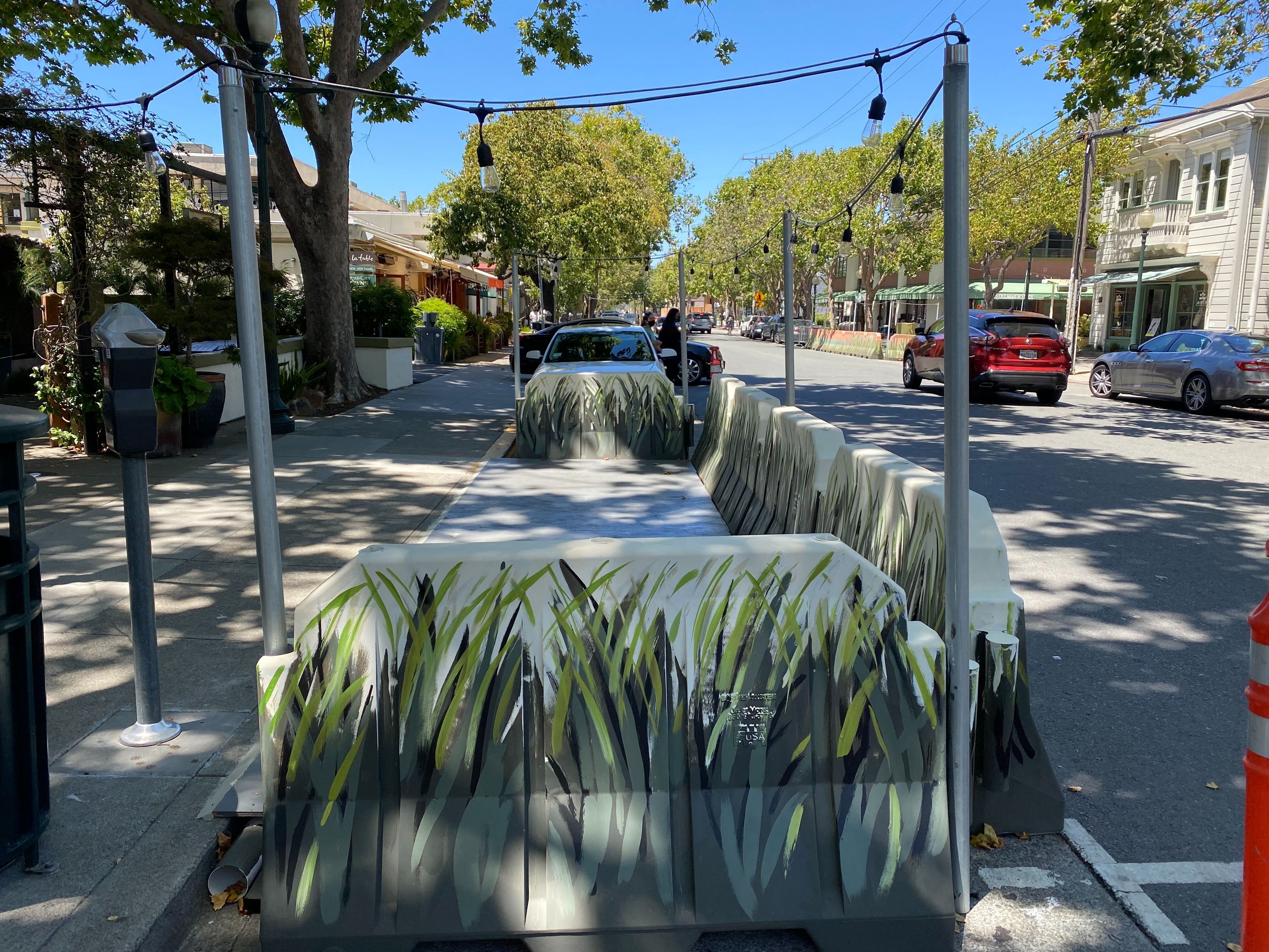 an empty parklet for outdoor dining, painted with a pattern to look like grass