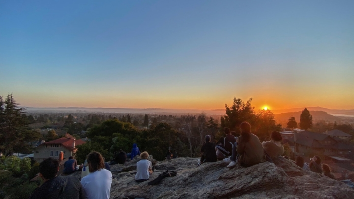 people perched on rock hill watching the sunset