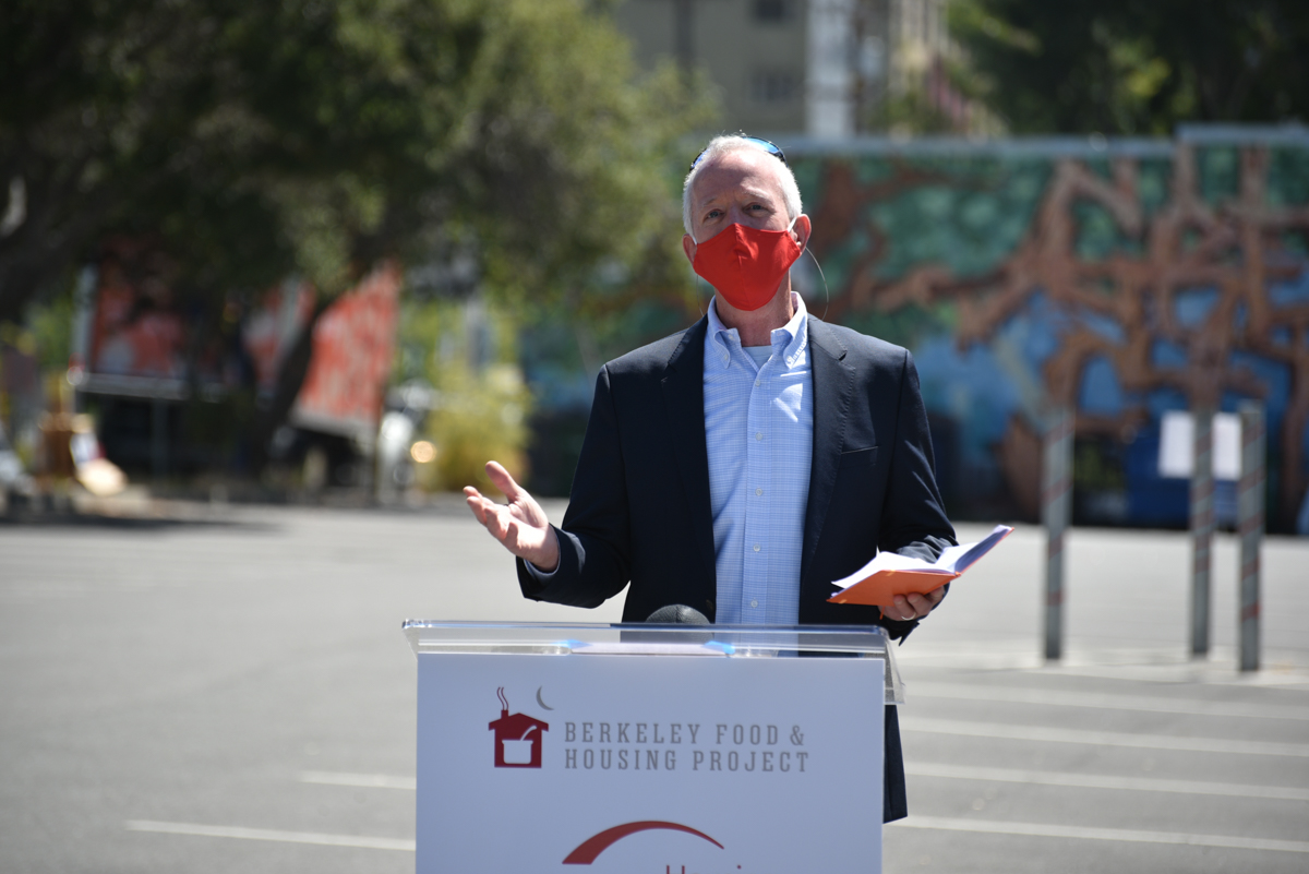 A man wearing a red mask speaks at a podium