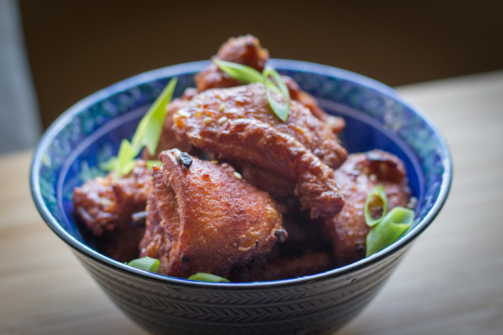A bowl of Mochiko chicken, garnished with green onion and sesame seeds. Photo: Benjamin Seto