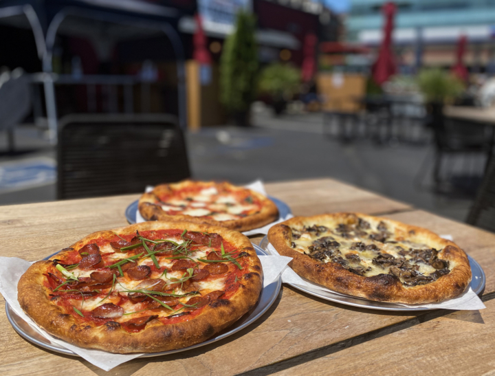 Three pizzas — pepperoni, mushroom and Margherita — sit on a table on the outdoor patio of Honor Kitchen and Cocktails in Emeryville.