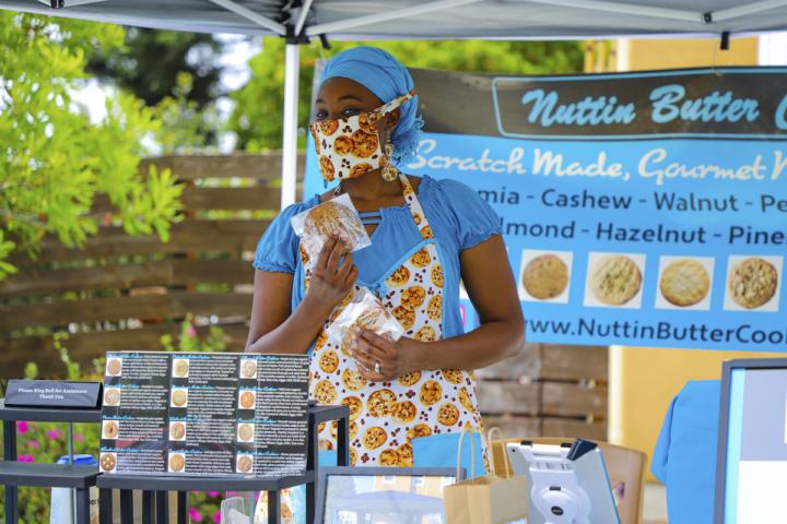 Wearing a cookie-print mask and apron, Whitney Singletary sells Nuttin' Butter Cookies at a booth in front of her house on Dwight Way in Berkeley.