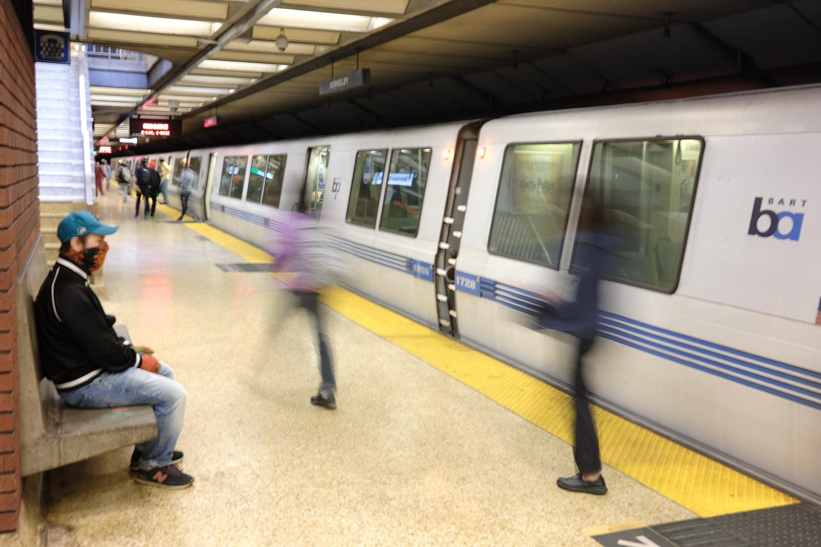 A man sits on a bench as BART passengers exit a train after arriving in Downtown Berkeley. August 26, 2020. Photo- Pete Rosos