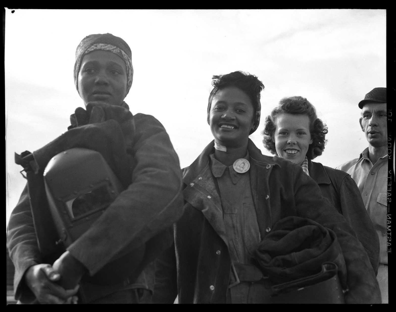 Women line up for paychecks-Richmond Shipyards Richmond, CA, Circa 1942. Dorothea Lange. Film negative, Gift of Paul S. Taylor 5 in x 4 in., A67.137.42080.4 © The Dorothea Lange Collection, the Oakland Museum of California. Digitized for the Oakland Museum of California 2019 Luce Grant