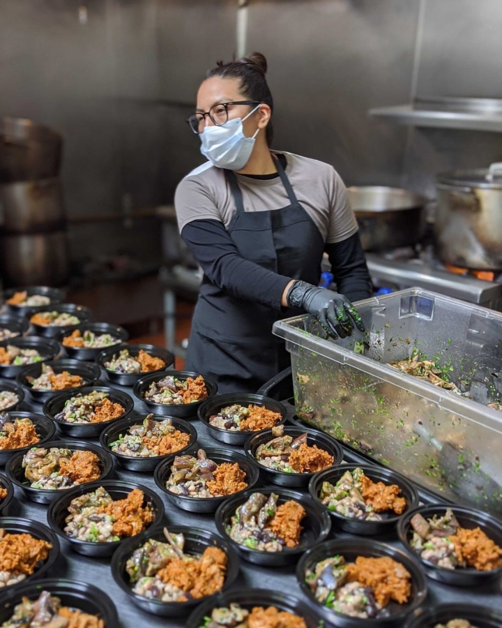 A Fare Community Kitchen worker prepared to-go meals to donate to the YMCA East Bay