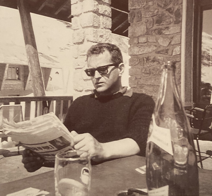 Hal Goldberg in the 1950s or 1960s in sepia toned photo sitting at cafe reading newspaper