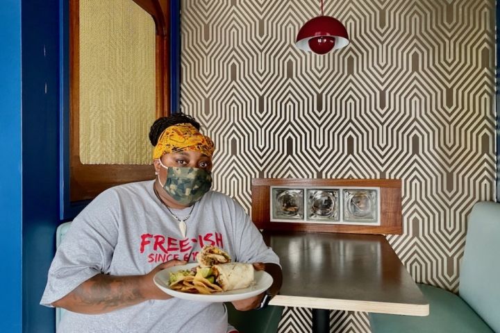 Lala Harrison, chef-owner of Jusla Eats, sits at a booth with a plate of food at Palmetto in Oakland. Photo: Sarah Han