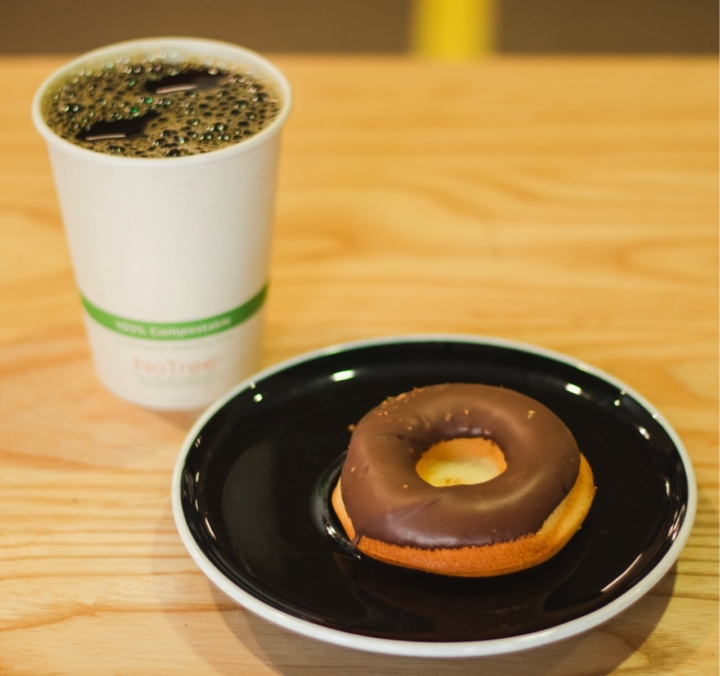 A paper cup of 1951 Coffee Company coffee and a Third Culture chocolate mochi donut on a black plate.