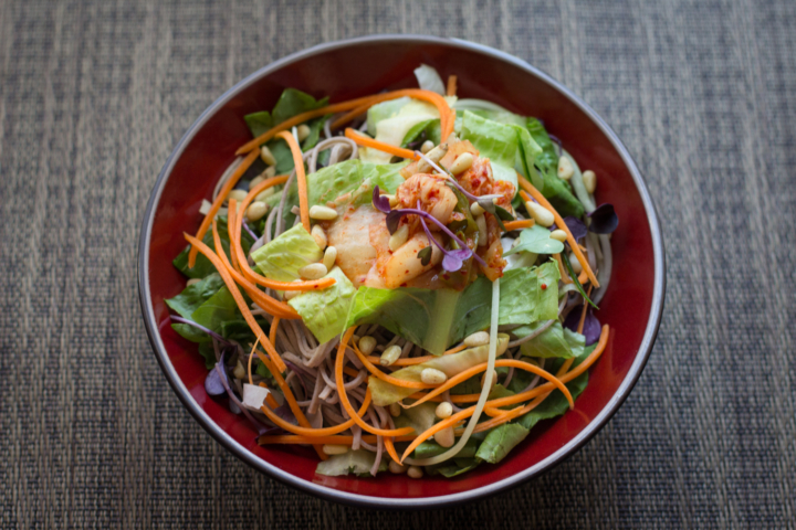 A bowl filled with soba noodles, julienned carrots, lettuce, pine nuts, kimchi and microgreens.