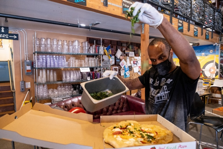 New Parkway employee Italo B sprinkles chopped basil onto a pizza made for the New Parkway's food program. Photo: Pete Rosos