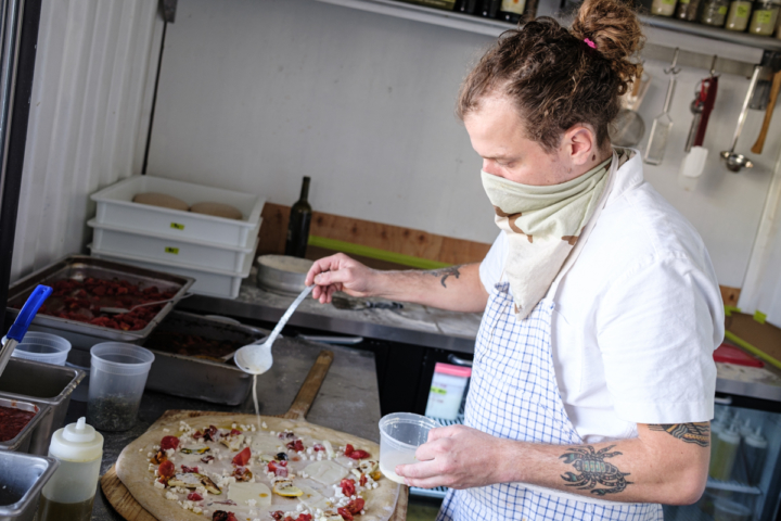 Pizza chef Josh Maes sprinkles a garlic cream sauce over a pizza special. Photo: Pete Rosos