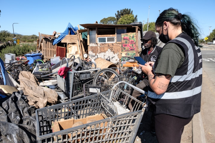 a census worker in front of several shopping carts, talking to an unhoused resident